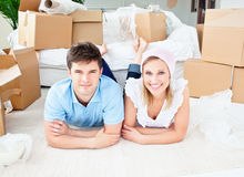 Joyful couple lying on floor after unpacking boxes
