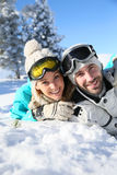 Joyful couple lying in the snow Royalty Free Stock Photo