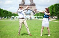Joyful couple playing near the Eiffel tower Royalty Free Stock Photography