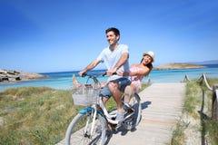 Joyful couple in pontoon riding bike together. Man giving bike ride to girlfriend on beautiful Island Stock Image