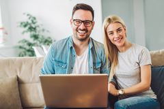 Joyful couple relax and work on laptop computer at modern living room. Indoor home, looking at camera Royalty Free Stock Images