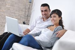 Joyful couple relax and work on laptop at home. Joyful couple relax and work on laptop computer at modern living room indoor home Royalty Free Stock Photo