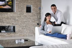 Joyful couple relax and work on laptop at home Royalty Free Stock Photos