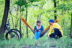Joyful couple rests after riding a bikes in the forest. On a awesome sunny day, relaxing in a hammock and talking  - wonderful weekend in nature Royalty Free Stock Image