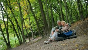 Joyful couple of retired tourists having rest in the wood. Active leisure time. Cheerful smiling aged couple of tourists sitting in the forest and embracing each stock footage