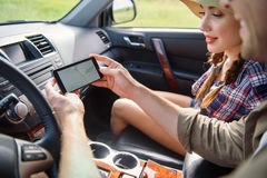 Joyful couple searing for location by phone. Young tourists are using smartphone navigation map in car. They are sitting and smiling Royalty Free Stock Image