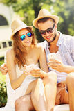 Joyful couple sitting on a bench with smartphones Royalty Free Stock Photo