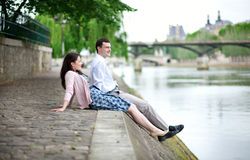 Joyful couple sitting on the embankment Royalty Free Stock Image