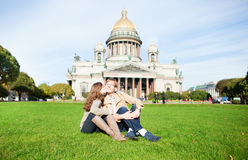 Joyful couple sitting near St. Isaac's cathedral Stock Photos