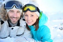 Joyful couple in ski outfit having fun lying in snow Royalty Free Stock Image