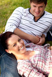 Joyful couple of students sitting on grass. In their campus Royalty Free Stock Photos