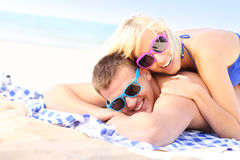 Joyful couple sunbathing at the beach Stock Photography