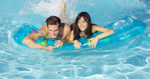 Joyful couple swimming together on floatie in pool Royalty Free Stock Photos