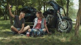 Joyful couple taking selfie on phone by motorbike stock video