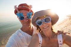 Joyful couple of travelers in funny sunglasses taking selfie Stock Photo