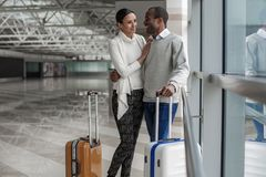 Joyful couple are traveling with suitcases. Full of love. Positive passionate young men and women are standing together with luggage at airport hall. They are Royalty Free Stock Photography