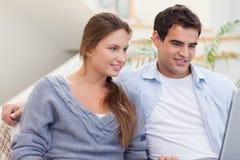 Joyful couple using a laptop Stock Photos