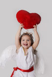 Joyful cupid girl holds plush heart over head Royalty Free Stock Image