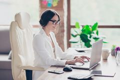 Joyful cute beautiful attractive glad clever manager is sitting stock photography