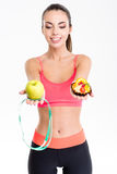 Joyful cute fitness woman making decision between apple and cake Royalty Free Stock Photography