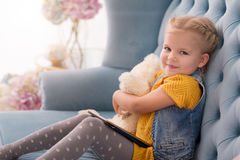 Joyful cute girl holding an electronic book in her knees Stock Photography