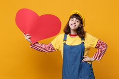 Joyful cute girl teenager in french beret, denim sundress holding big empty blank red heart isolated on yellow wall. Background in studio. People sincere royalty free stock image