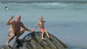 Daddy and boy sit on stones waving hands against azure ocean