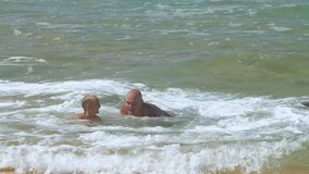 Daddy plays with son in rolling sea waves at exotic resort