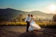 Joyful dancing couple of newlyweds in sunglasses on the road at the background of the mountains during the sunset. Joyful dancing couple of newlyweds on the Royalty Free Stock Photo
