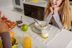 Joyful daughter enjoying talk with mom in kitchen. This is my favorite food. Cute girl is having breakfast with her mother. She is listening to her with interest stock image