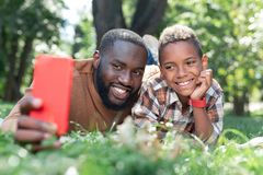 Joyful delighted father and son smiling for a photo. Happy memories. Joyful delighted father and son smiling while taking photos together royalty free stock photo