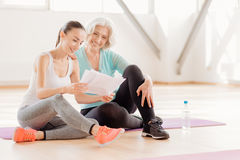 Joyful delighted women reading the workout plan Royalty Free Stock Photo