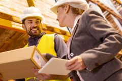 Joyful delivery man talking to the client royalty free stock photography