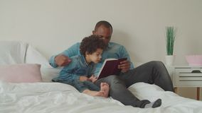 Joyful diverse family reading a book lying on bed