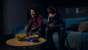 Laughing boys eating popcorn and watching comedy. Joyful diverse teen friends in casual clothing nickering during comical scenes of movie sitting on sofa in stock video
