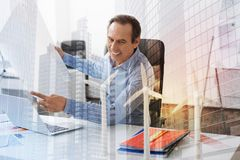 Joyful eco engineer sitting in the office Stock Images