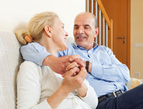 Joyful elderly couple together on sofa in home interior Stock Photos