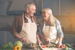 Joyful elderly husband and wife cooking with enjoyment