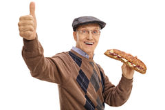 Joyful elderly man having sandwich and making thumb up sign stock images
