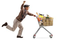 Joyful elderly man pushing a shopping cart filled with groceries. And holding his hand up isolated on white background royalty free stock photos