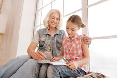 Joyful elderly woman drawing with her granddaughter Stock Images