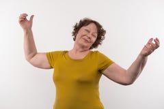 Joyful elderly woman feeling happy. Positive emotions. Joyful elderly woman gesticulating with her hands while feeling happy Royalty Free Stock Photography