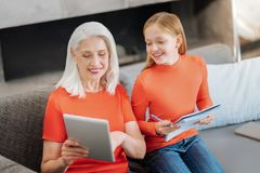 Joyful elderly woman helping her granddaughter. Home lessons. Joyful nice elderly women sitting on the sofa and holding a tablet while helping her granddaughter Stock Images
