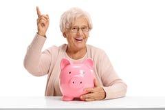 Joyful elderly woman with a piggybank pointing up Royalty Free Stock Image