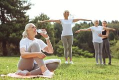 Joyful elderly woman taking a sip of water. Refreshing liquid. Joyful positive elderly women sitting on the yoga mat and taking a sip of water while having a stock photography