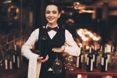 Joyful elegant waitress holding bottle of red wine and glasses, standing near bar. royalty free stock image