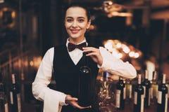 Joyful elegant waitress holding bottle of red wine, standing near bar. Sommelier tasting wine in restaurant royalty free stock images
