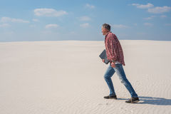 Joyful energetic man is walking through the desert with a laptop. In his hands. Concept - you must go to your goal and enjoy it, no matter what around stock image