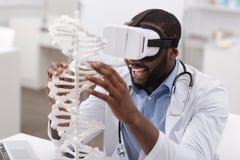 Joyful enthusiastic man touching the gene model Royalty Free Stock Photography