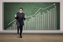 Joyful entrepreneur with financial graph. Happy young businessman expressing his success in front of financial graph on the blackboard Stock Image